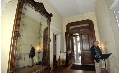 """At the Enoch Pratt House, former U.S.Sen. Paul Sarbanes, who happened to be taking the tour, is reflected in the Bonaparte mirror from the Patterson/Bonaparte family. The Pratt House was one of 61 buildings open for tours Saturday as part of an effort to showcase the best in architecture. Sarbanes said the whole project is """"a terrific idea."""""""