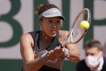 Japan's Naomi Osaka returns the ball to Romania's Patricia Maria Tig during their first round match of the French open tennis tournament at the Roland Garros stadium Sunday, May 30, 2021 in Paris. She later withdrew from the tournament citing her mental health. (AP Photo/Christophe Ena)