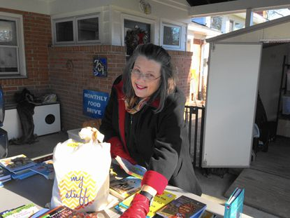 """Knollwood-Donnybrook resident Jo Marvan shows a """"My Stuff"""" bag in her garage. Each bag is filled with books, toiletries, a throw blanket, a toy and a game for children at the Baltimore County Family Crisis Center."""