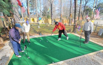 Bob Hedgebeth (Right center) has erected a putting green, a driving range, and other practice areas in his backyard.