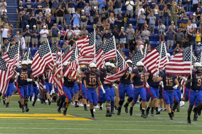Carrying U.S. banners, Navy Midshipmen storm the field to play against Air Force at the twentieth anniversary of the9/11/2001 terrorist attacks before the game against Air Force Sat., Sept. 11, 2021. (Karl Merton Ferron/Baltimore Sun Staff)