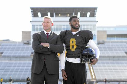 Will Huff, left, Towson University's Deputy Director of Athletics for Operations, and Wardell Turner scholarship recipient Monty Fenner pose at Towson's Johnny Unitas Stadium. Huff has organized a day to honor veterans at the college Nov. 5 as part of that day's football game.