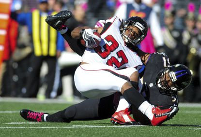 Ravens linebacker Daryl Smith tackles Falcons running back Jacquizz Rodgers.