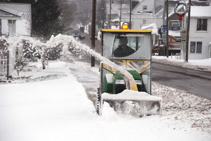 Park Superintendent Heath Martin used a tractor with a snow thrower attachment to clear the walks of Main Street in Grantsville in 2008.