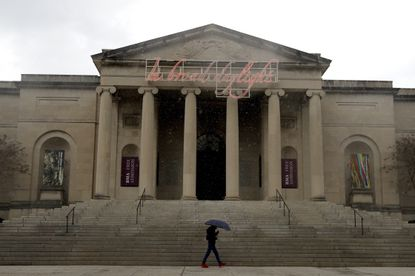 In this April 21, 2020 file photo, a man covers himself from rain with an umbrella as he walks in front of the Baltimore Museum of Art in Baltimore.