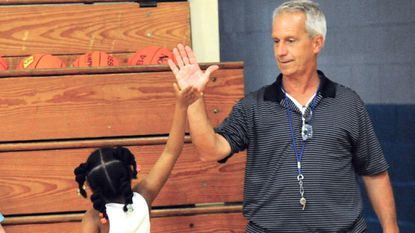Morgan Webb, 6, high-fives Jerry Georgiana during Mr. Jerry's Summer Basketball Camp at West Middle School, in Westminster.