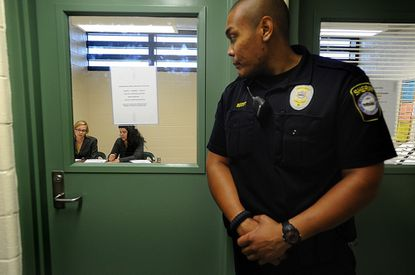 Officer Rex Scott, Jr. looks in on Stephanie Salter and Kimberly King of the Carroll County Public Defender's Office as they interview a client for his bail review at the Carroll County Detention Center in Westminster Thursday.