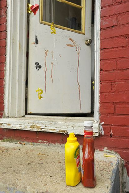 Blood can be seen spattered on the back door at the scene of a backyard cookout in East Baltimore at which 12 people were shot and wounded.