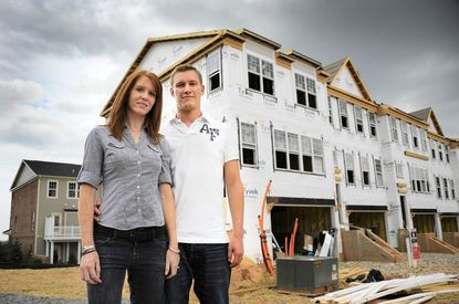 Rachel and Joshua Jennings pose outside their unfinished home, which is being built at The Pointe at ArundelPreserve.