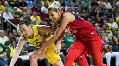 Seattle Storm forward Breanna Stewart, left, and Washington Mystics guard Elena Delle Donne dive for a loose ball in the first half of a WNBA basketball game, Sunday, July 8, 2018, in Seattle. Seattle won 97-91.