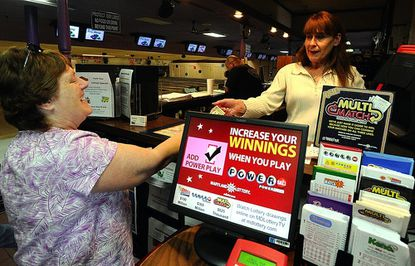 Barbara Bostian buys a lottery ticket from Kay Reaver at Thunderhead Bowl & Grill on Wednesday.