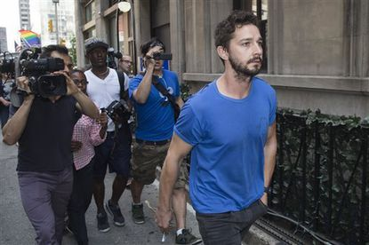 "Actor Shia LaBeouf walks through the media after leaving Midtown Community Court following his arrest the previous day for yelling obscenities at a Broadway performance of ""Cabaret"", Friday, June 27, 2014, in New York. The 28-year-old, who starred in the first three ""Transformers"" movies, was arrested on charges of disorderly conduct and criminal trespass. He's due back in court July 24. (AP Photo/John Minchillo)"