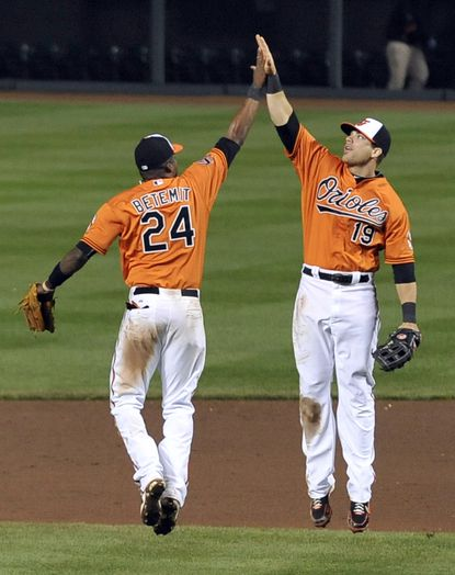 The Orioles' Wilson Betemit, left, and Chris Davis celebrate their 10-1 win over the A's. Davis had three hits, including a solo homer, and drove in four runs.