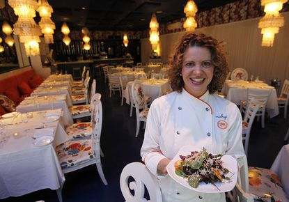 In this photo taken Thursday, Dec. 9, 2010, chef Michelle Bernstein holds a roasted beet salad at Michy's in the MiMo section of Miami. For travelers looking for respite from South Beach clubs and the oh-so chic Design District, the offbeat Miami Modern District -- also known as MiMo -- offers a welcome change of pace.