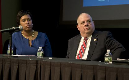 Washington D.C. Mayor Muriel Bowser and Maryland Governor Larry Hogan listen to Virginia Governor Terry McAuliffe speak at a Regional Opioid and Substance Abuse Summit held at the Maritime Institute in Linthicum Heights.