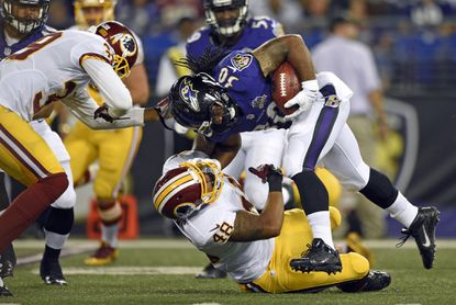 Ravens running back Terrence Magee (30) is tackled by Washington Redskins linebacker Dyshawn Davis (48) in the second half of a preseason game, Saturday, Aug. 29, 2015, in Baltimore.