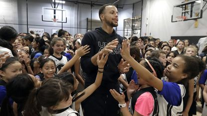 The Golden State Warriors' Stephen Curry, center, greets basketball camp participants in Walnut Creek, Calif., in August. A letter from a 9-year-old girl has helped Curry fix online access to his Under Armour shoes for kids. His Curry5s were marketed only to boys.