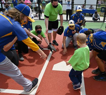 Members of the Aberdeen JV and Varsity baseball teams and fellow Miracle League players help Miracle League baserunner Andrew Tavegia with a little direction as he comes home after a big hit in the game at the Miracle League of Harford County Field at Schucks Regional Park in Bel AIr Saturday April 24, 2021.