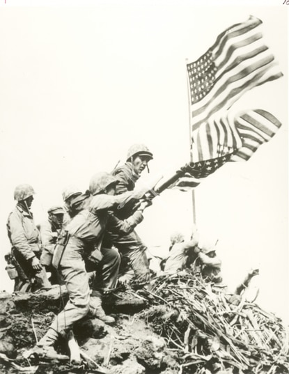 U.S. Marines raise a large American flag to replace a smaller flag first raised at the summit of Mount Suribachi on Iwo Jima, Feb. 23, 1945.