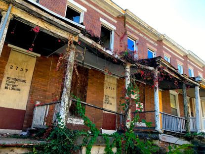 Three dilapidated, vacant houses mar a block of occupied homes on Rayner Avenue in West Baltimore.