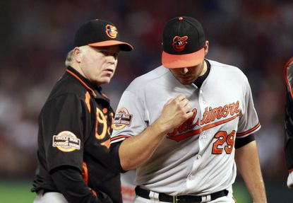 Tommy Hunter exits Wednesday night's game in the fourth inning as manager Buck Showalter looks on from the mound.