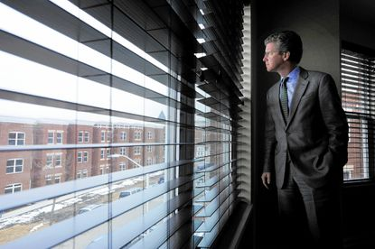 Shaun Donovan, U.S. secretary of Housing and Urban Development, surveys the 400 block of E. 20th St. as he tours newly constructed homes in the area.