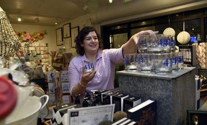 Kohli Flick, owner of Becket Hitch Home Furnishings, arranges a display of glasses in her store.