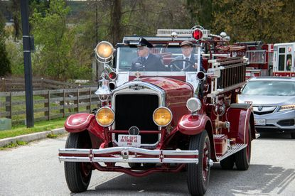 "An antique fire engine, driven by Josh Christina and with passenger Dawn Banister, at the April 17 memorial service for former Baltimore County Fire Chief Elwood ""Woody"" Banister."