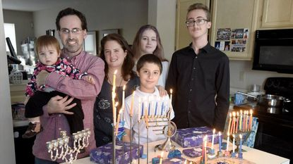 The Feldman family, from left, 11-month-old Evelyn, Stuart, Deborah, Joey, 10, Sarah, 14, and Jacob, 15, stand in their kitchen near menorahs, dreidels and Hanukkah gifts.