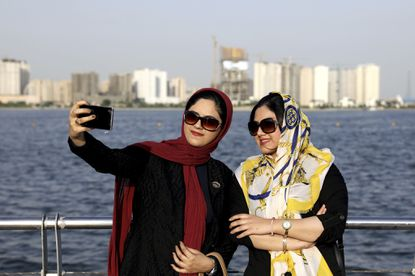 Iranians take selfie around of the Persian Gulf Martyrs lake, west of Tehran, Iran last summer. A few daring women in Iran's capital have been taking off their mandatory headscarves, or hijabs, in public, risking arrest and drawing the ire of hard-liners. Many others stop short of outright defiance and opt for loosely draped scarves that show as much hair as they cover. More women are pushing back against the dress code imposed after the 1979 Islamic Revolution, and activists say rebelling against the hijab is the most visible form of anti-government protest in Iran today.