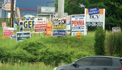 """Election campaign signs are clustered on a vacant property at the corner of Harford Road and the Bel Air Bypass in Fallston, a site known in past campaigns as """"Boot Hill."""" Early voting for the June 26 primary election begins Thursday and runs through June 21."""