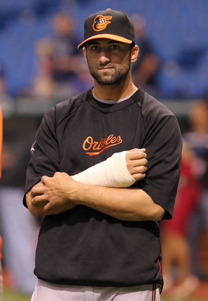 Nick Markakis holds his right arm, which is in a cast following surgery earlier Friday.