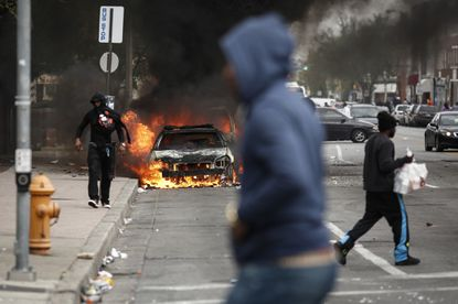 People walk past burning cars near the intersection of Pennsylvania Avenue and North Avenue Monday in Baltimore. Violence erupted following the funeral service for Freddie Gray, who died a week after being arrested by Baltimore police.