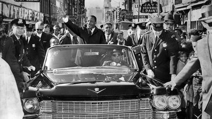 The Rev. Martin Luther King Jr. greets thousands of admirers on a motorcade tour up Baltimore's North Gay Street in 1964.
