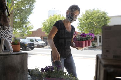 Kyanne Garrigan, owner of Full Heart Solutions, placed flowers on a planter outside her store as she prepared to receive customers at her establishment on Main Street in Bel Air last Friday, when some small business and retailers were allowed to reopen with some guidelines after Maryland Gov. Larry Hogan lifted the state's stay-at-home order.
