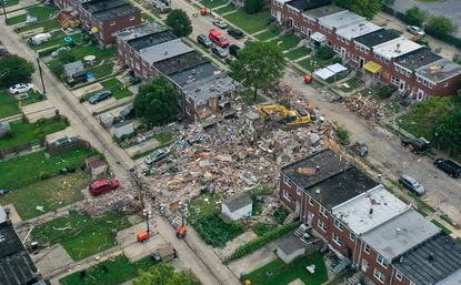 Workers continue to assess the scene in Baltimore's Reisterstown Station neighborhood a day after gas explosion leveled three homes Monday morning. No cause has been determined but the tragedy raises questions about whether the city's leaking pipelines are being replaced fast enough.