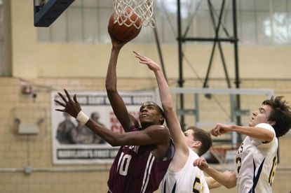 Kodye Pugh drives to the hoop past a pair of Catonsville defenders.