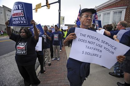 U.S. Postal workers rally outside U.S. Rep. Elijah E. Cummings' 7th District office in Catonsville to protest federal mandates that require the U.S.P.S. to fund future pension obligations that are resulting in branches closure and layoffs.