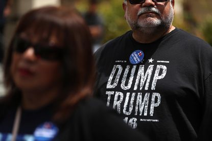 """A supporter of Democratic presidential candidate former Hillary Clinton wears a """"Dump Trump"""" shirt before a campaign rally at Harrell College in Riverside, California."""