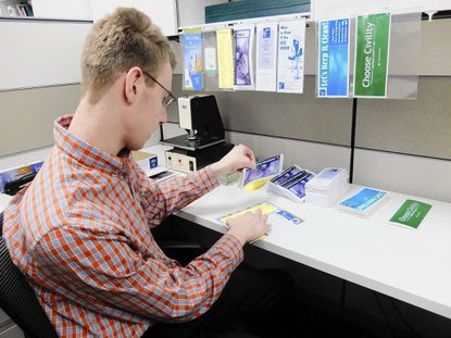 Craig Knill, 19, a senior at Glenelg High School, puts together pamphlets at the Howard County Council offices Friday, April 11.
