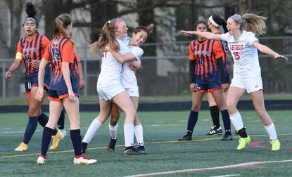 Glenelg's Kaila Spence, center, is embraced by Molly Nichols as teammate, Stephanie Lathrop, right, joins in to celebrate a first half goal scored against Reservoir during the girls soccer county championship game at Wilde Lake High School on April 16.