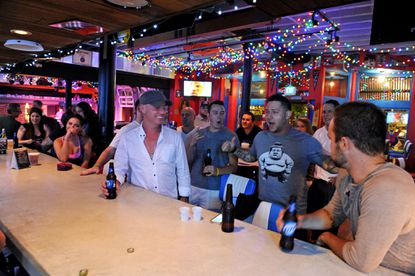 Patrons share a laugh at Tin Roof Baltimore in Power Plant Live on a recent Wednesday night.