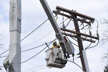 David Brown, a BGE lineman, works to ground power lines on Charlesmeade Avenue.