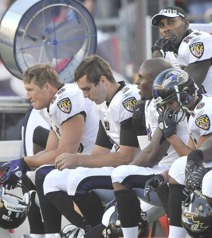 The Ravens bench, including Todd Heap, Joe Flacco and Anquan Boldin, react to the Patriots' final first down in overtime, which led to their game-winning field goal.