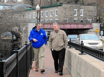 Ryan Miller, left, and Howard County Executive Alan Kittleman, right, walk on the bridge overlooking the Patapsco river with Main Street behind them.