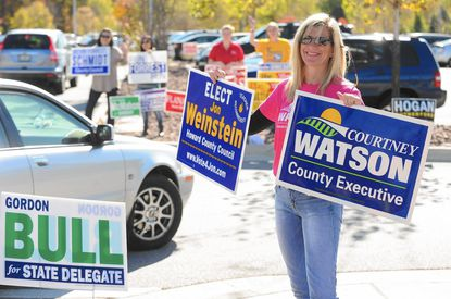 Cindy Ardinger, of Ellicott City, holds campaign signs for traffic pulling into the Miller Branch Library during early voting Oct. 27.