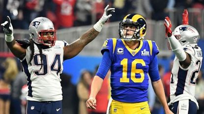 Rams quarterback Jared Goff watches after throwing an intereption in the fourth quarter as Patriots Adrian Clayton (94) and Duron Harmon celebrate.