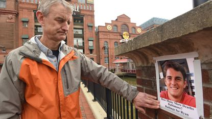 Jim Schroeder smooths the tape after posting one of several photos of his son, Ryan, near the scene where he drowned in the Inner Harbor on Feb. 1, 2018. Jim and his wife, Anne, have campaigned for safety railings to prevent further drownings.