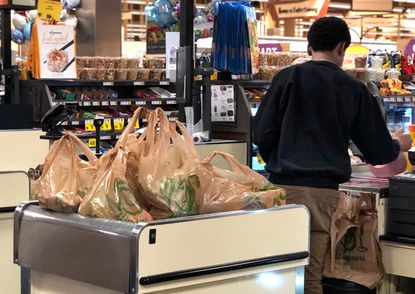 A cashier in Wegmans in Columbia uses plastic bags for a customer's groceries in the check-out line. As Howard County prepares for the Oct. 1 implementation of a 5-cent fee on disposable plastic bags, business owners are readying for what the change in legislation means for their day-to-day operations.