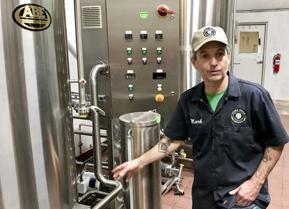 Mark Moody, co-owner and head brewer for Double Groove Brewing in Forest Hill, stands near the boil kettle and chiller in the brewery Saturday as he explains the beer brewing process.